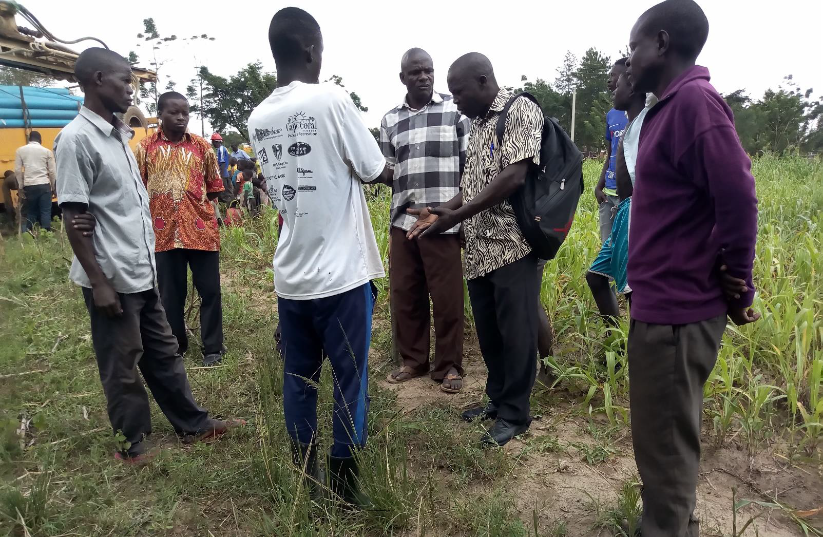 The committee and local leaders assess the site for the drilling